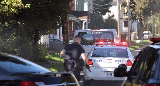 In this image pulled from the video by Max Schulte, an officer runs to follow  the van after shots were fired at it on Forester Street.