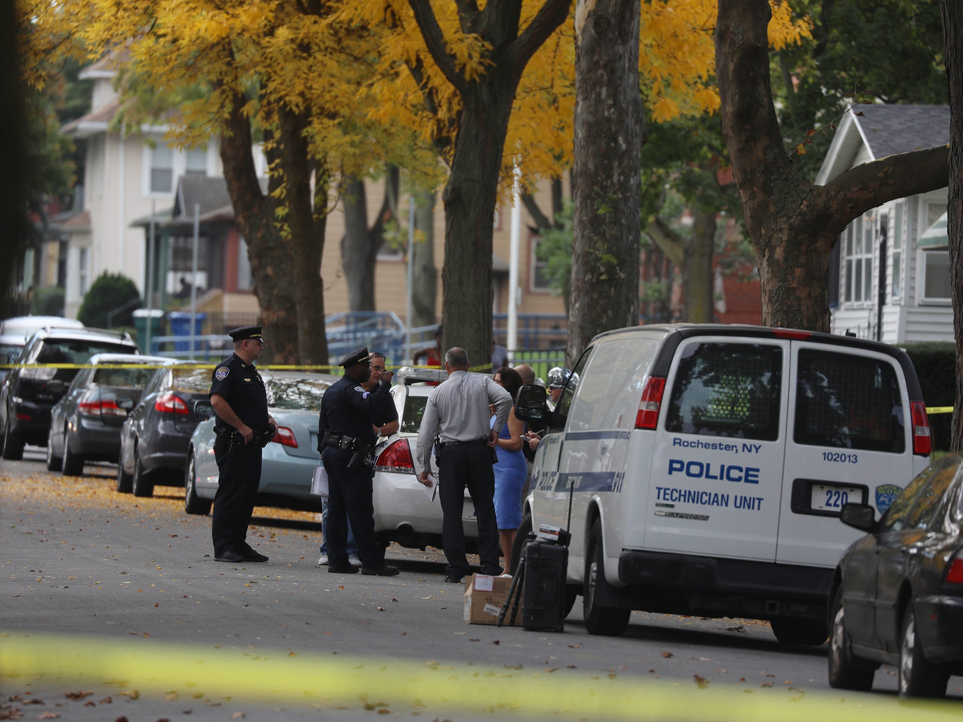Police collect evidence at the scene of the Post Ave. shooting.