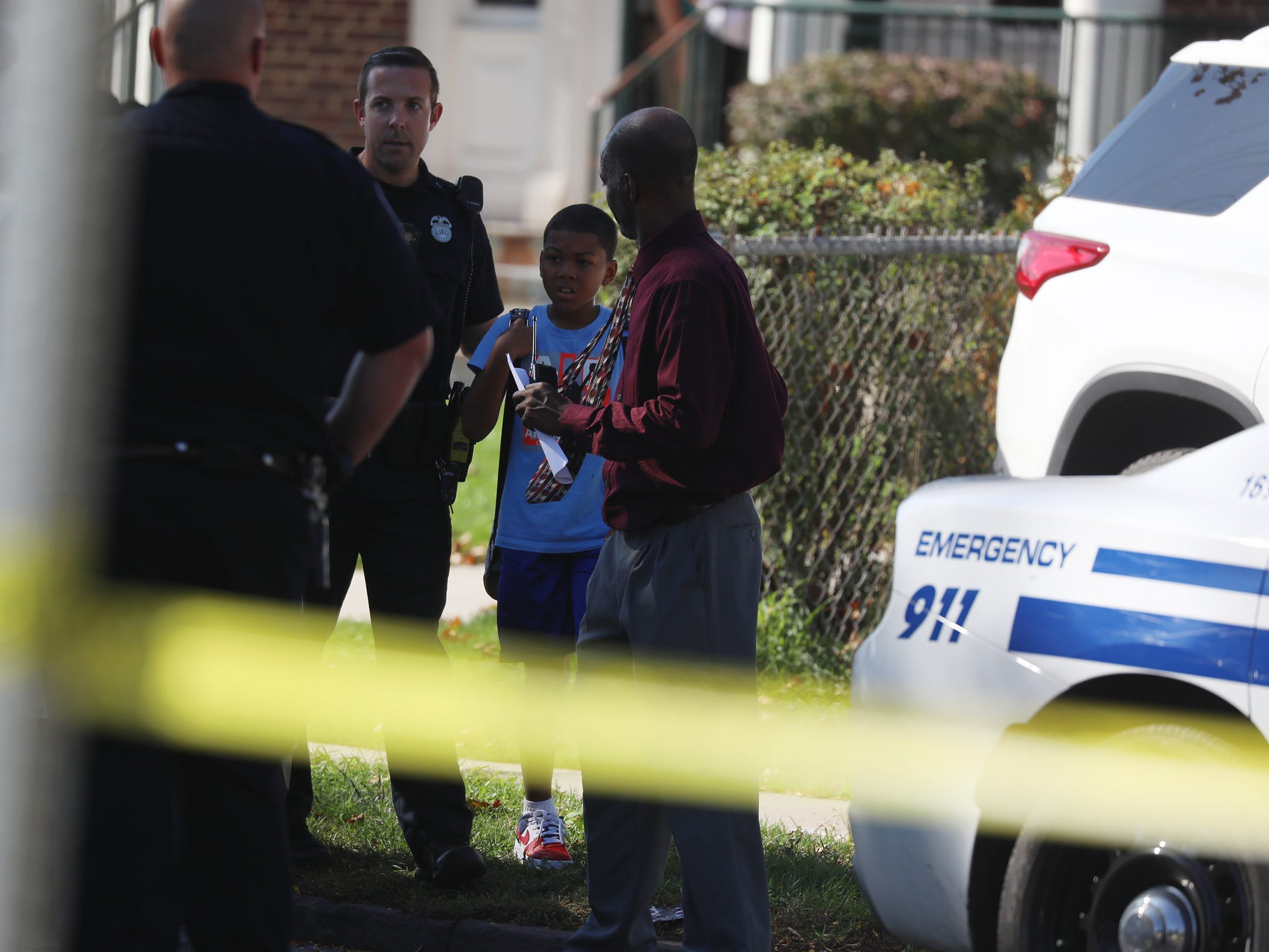 A boy is escorted from School 25 by police and school personnel across Goodman St. to Powers St. to his waiting family.