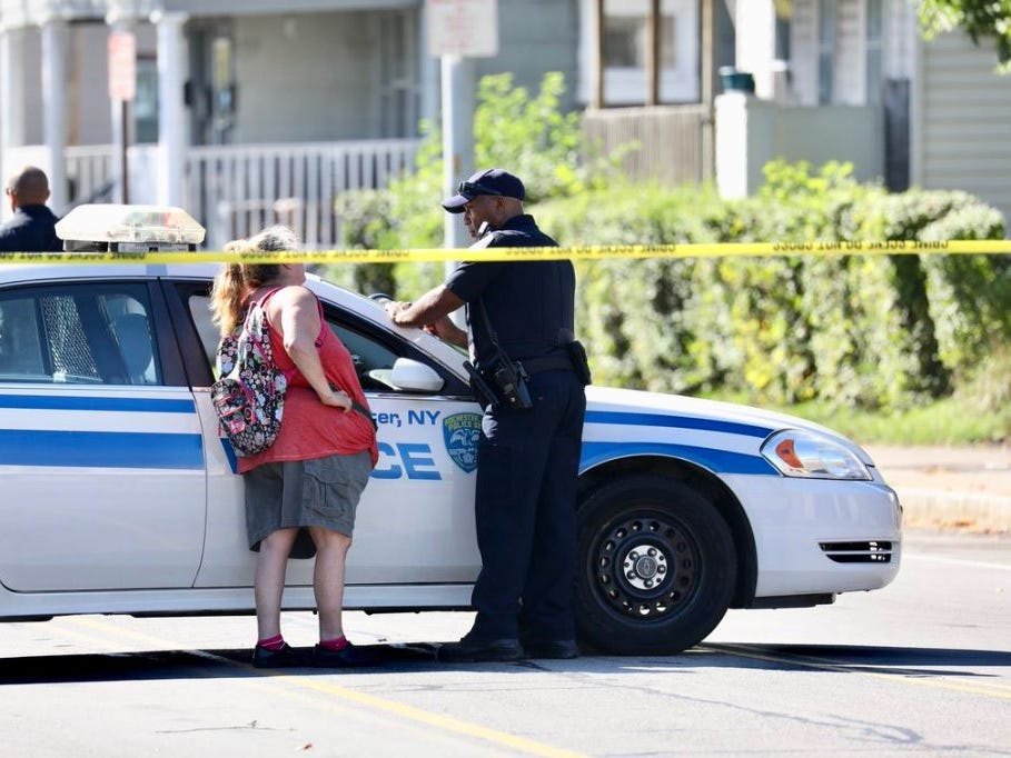 A woman speaks to an officer in the Goodman and Bay streets area.