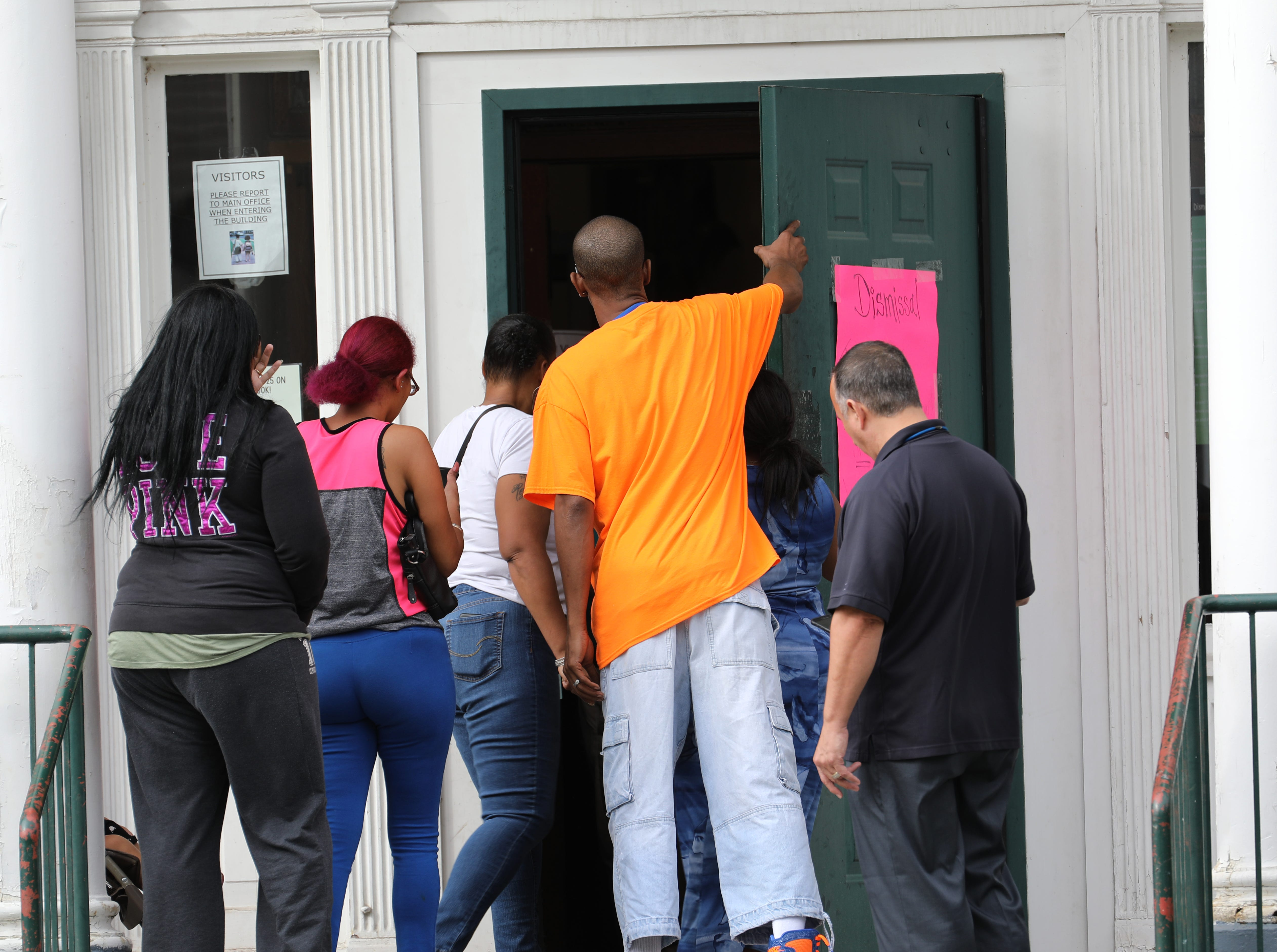 Parents enter School 25 in Rochester to collect their children after a man was shot near the playground at the school.