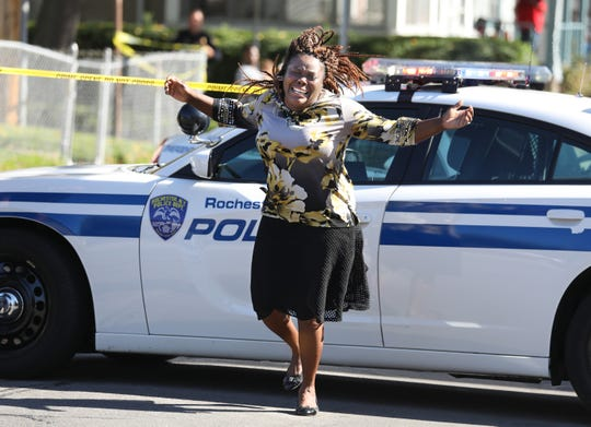 Juliet Blake-Lavan, Rochester, aunt of shooting suspect, reacts to news that he was killed in a shoot out with police as she stops at a roadblock near the scene on Bay Street in Rochester Wednesday, Oct. 10, 2018.
