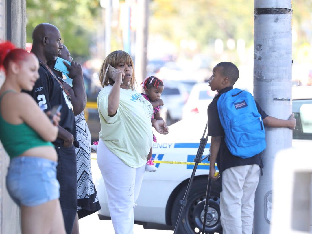 Brandi Latham holds her one-year-old daughter Angelec, next to her son Jayden, 9, as she tries to find out if she can get back to her house on Bay and Goodman Streets. Police say a gunman shot three family members before leading police on a high-speed pursuit that ended with a fatal shootout.