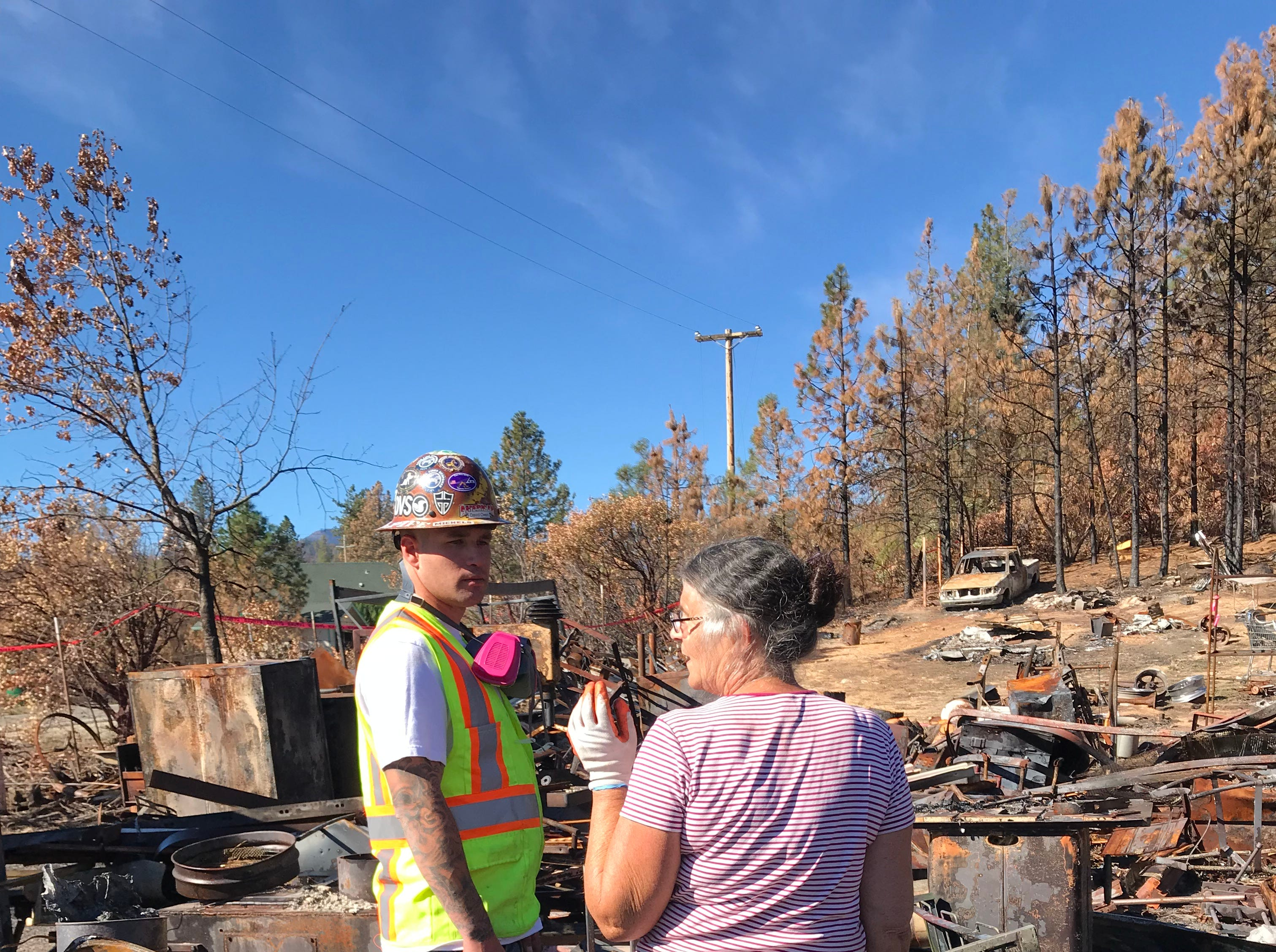 Marci Fernandes speaks with CalRecycle worker on debris removal day at her home in Keswick on October 9, 2018. She wants to save some of the pieces of machinery her late husband, Larry Allen, used to build replicas of historic cannons.