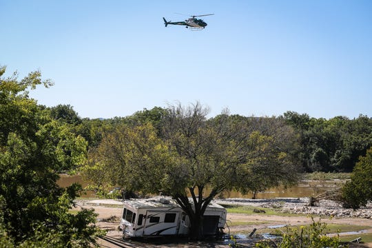 Search and rescue helicopter flies by the RV park hit in Monday's South Llano River flooding Wednesday, Oct. 10, 2018, in Junction.