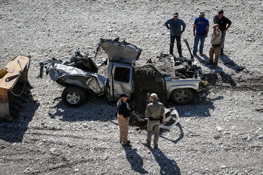 Search and rescue crew look over a truck buried in the sand after South Llano River flooded Wednesday, Oct. 10, 2018, in Junction.