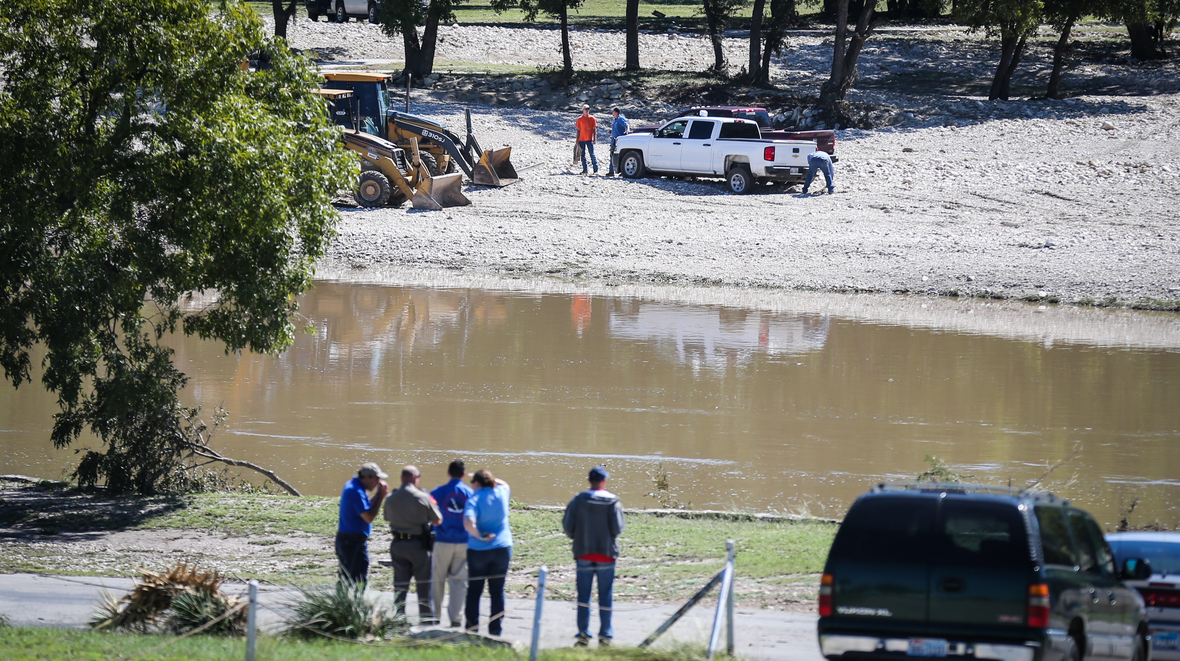 Search and rescue crew watch as backhoes dig for clues to whereabouts of the missing people after the South Llano River flooding Wednesday, Oct. 10, 2018, in Junction.