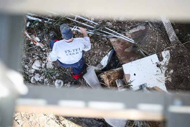Texas Task Force 1 member walks through debris to find the missing people after the South Llano River flooding Wednesday, Oct. 10, 2018, in Junction.