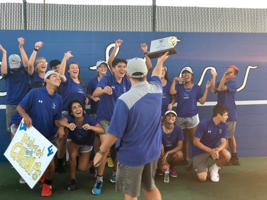Lake View head tennis coach Brandon Hettick, back to camera, presents the District 5-4A championship trophy to his team Tuesday, Oct. 9, 2018, at the Brandon Clark Tennis Complex.