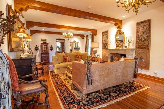The formal living room of 1107 Montecito Drive reveals open beams and two chandeliers.