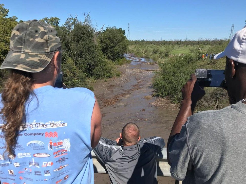 Residents watch flood waters flow into the North Concho River at the FM 2288 overpass at Grape Creek.