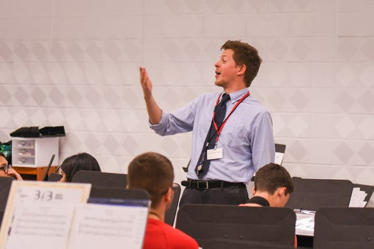 Snow Hill High School band director Matt Haelig conducts students during practice on Wednesday, Oct 10, 2018.