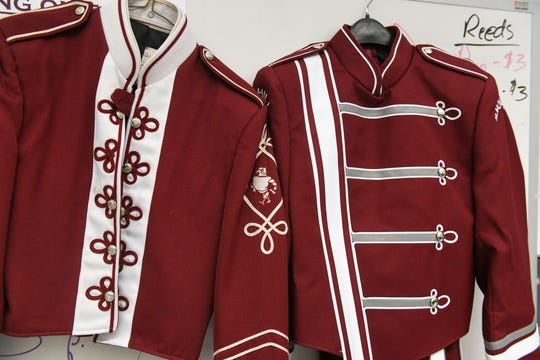 The new high school band uniform (right) hangs in Snow Hill alongside an old uniform that lasted the school for 33 years on Wednesday, Oct 10, 2018.