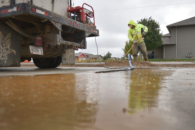 T&R Contracting employee Jeremiah Chasteen sweeps water out of the median on Ellis Road Wednesday, Oct. 10, in Sioux Falls. The major construction project won't be done till next spring because of bad weather.