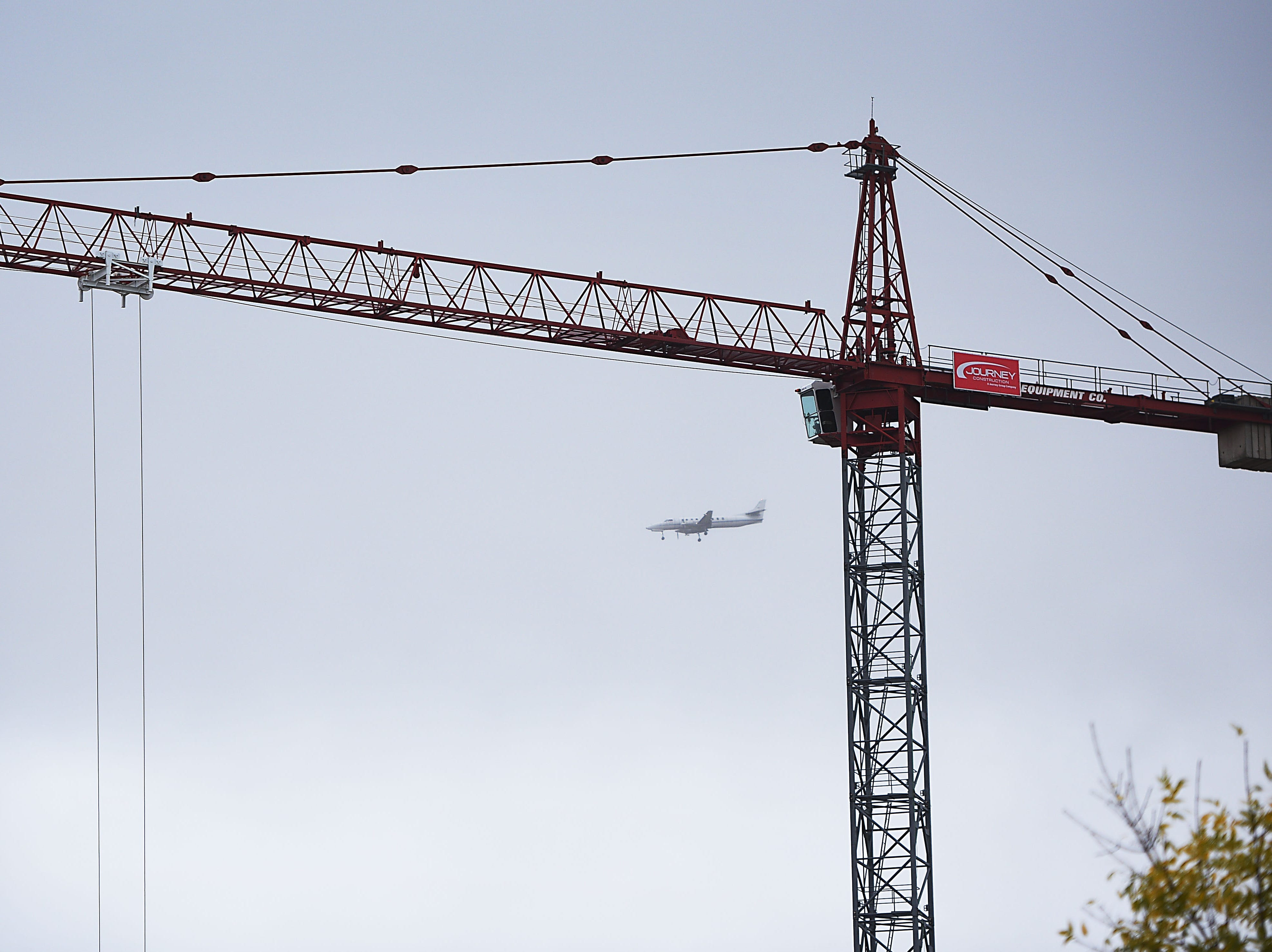 A plane flies by the massive crane that has been erected downtown Wednesday, Oct. 10, in Sioux Falls. The crane is used to erect steel in the Village on the River mixed use parking ramp.