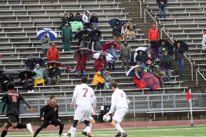 Fans brave the driving rain to watch Washington play Spearfish during Tuesday's semifinal game in Sioux Falls.