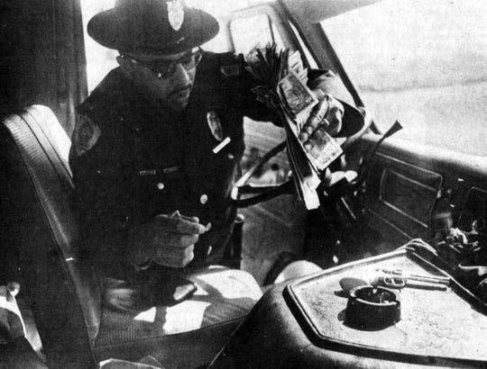 Lt. Walter Brown recovers money and cap gun from New Hope bank robbery in 1973. Photo was taken by Dennis Sutton, Staunton News Leader.