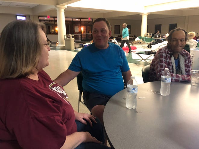 Tallahassee residents Gale Berry, left, and James Berry, middle, share conversation with Skip White, a Crawfordville resident, at the Lincoln High shelter ahead of Hurricane Michael early Wednesday morning.