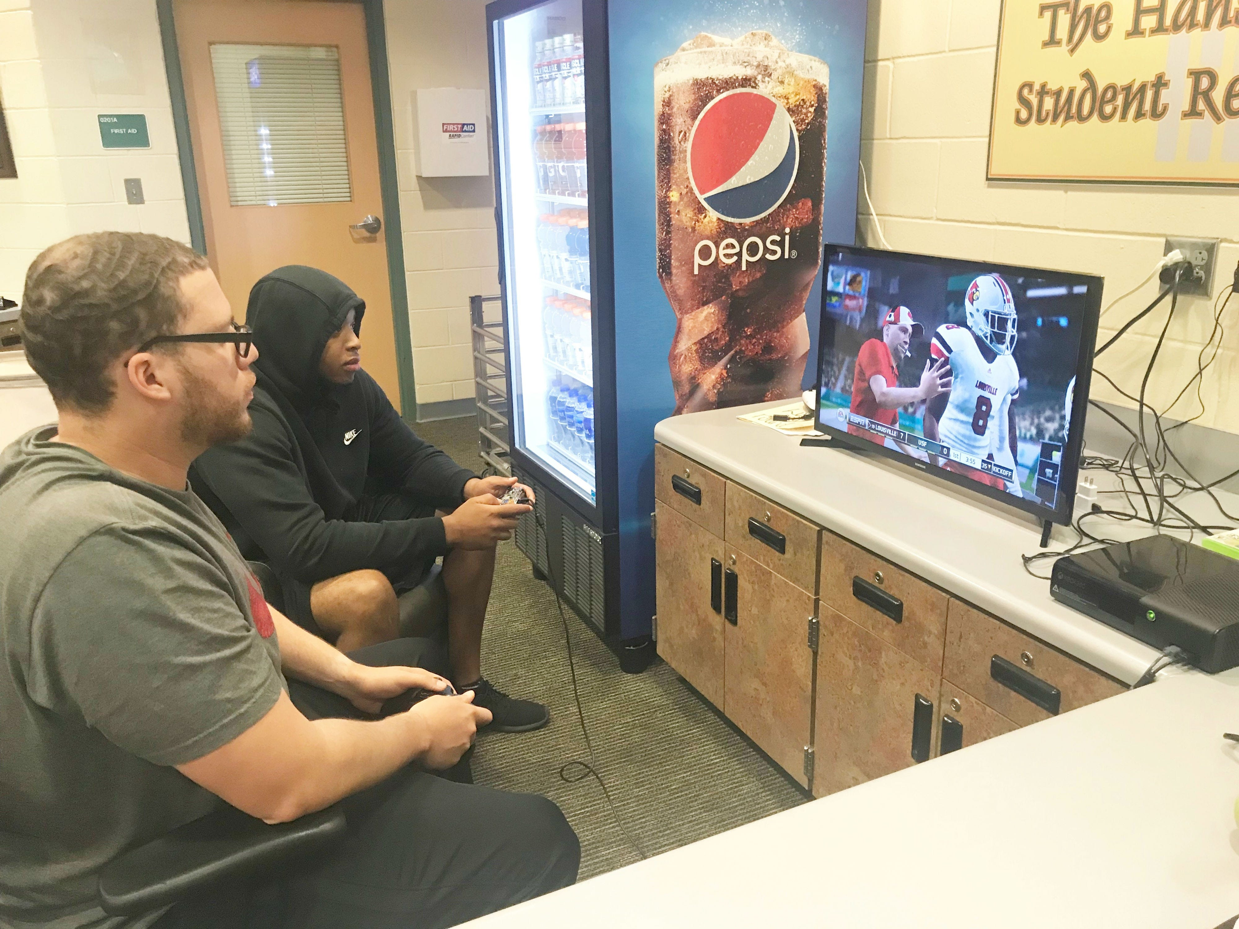 FAMU graduate assistant coaches Mateo Kambui (foreground) and Desmond Noird play NCAA Football on Xbox One. Kambui used Louisville while Noird played with South Florida. The Cardinals won 21-17.