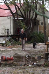 Day McGee surveys the damage to the house of her friend Mary Sinnock along U.S. 98. McGee was taking care of Sinnock's house while she was away in Indianapolis taking care of a friend. McGee got Sinnock's cat out last night.