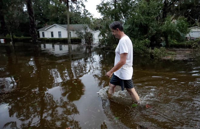John Gouge walks through flood waters as he goes to check on the post office Wednesday, Oct. 10, 2018, in St. Marks, Fla.