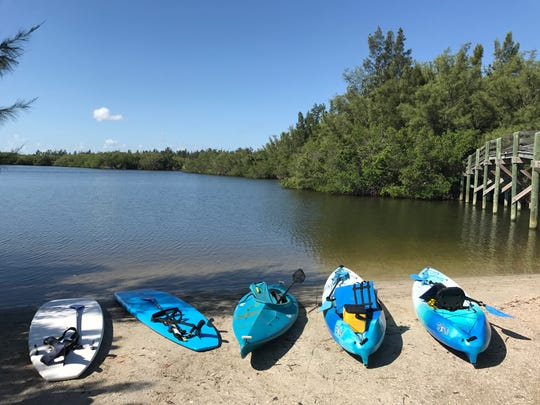 Kayaks and standup paddleboards wait to be launched at Round Island Riverside Park.