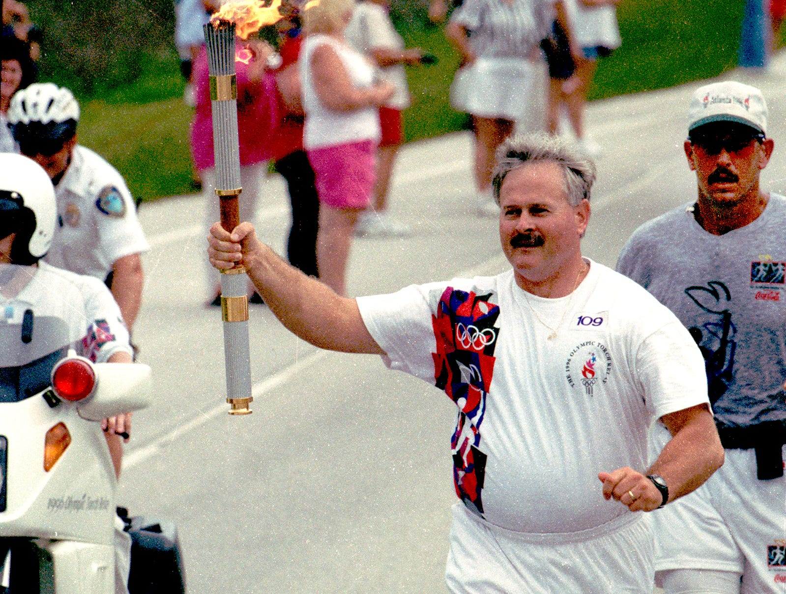 "July 6, 1996 - David Cherry was one of the 54 local torchbearers to make his way through Vero Beach as part of the historic trip through the downtown historic area. ""It's a thrill. The people yelling and cheering - you feel one with the world right at that moment, like there's nothing you can't do,"" said Cherry."