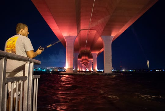 """Tim Gallagher, of Port Salerno, fishes for snook under the Roosevelt Bridge, seen lit pink during Breast Cancer Awareness Month, on Monday, Oct. 8, 2018, in downtown Stuart. Gallagher's mother, Lucinda Butler, died from cancer in September 2018. """"I want to try to put together something where one night we all go to fish with pink jigs,"""" he said, adding that he'd like to make it an event to raise funds for the nonprofit Cancer Research Institute. The local chapter of the American Cancer Society, Making Strides for Martin County, is also holding its annual fundraising walk in downtown Stuart on Oct. 26, 2019."""
