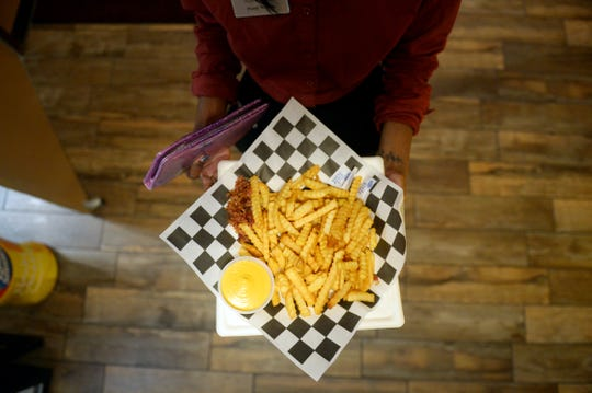 Nadine Laurent, an employee of Touchstar Cinemas Sabal Palms Luxury 6 in Fort Pierce, prepares to deliver a plate of French fries to a customer. The theater, which opened for business in August 2017, has large reclining chairs and a full-service bar.