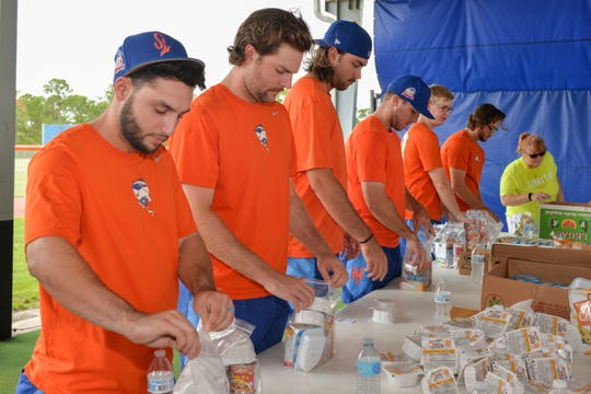 St. Lucie  Mets players Michael Paez, left, Mike Gibbons, David Peterson, Raphael Gladu, Dan Rizzie and Anthony Kay stuff food backpacks in assembly line style during the second annual Strike Out Hunger Night benefiting Treasure Coast Food Bank.