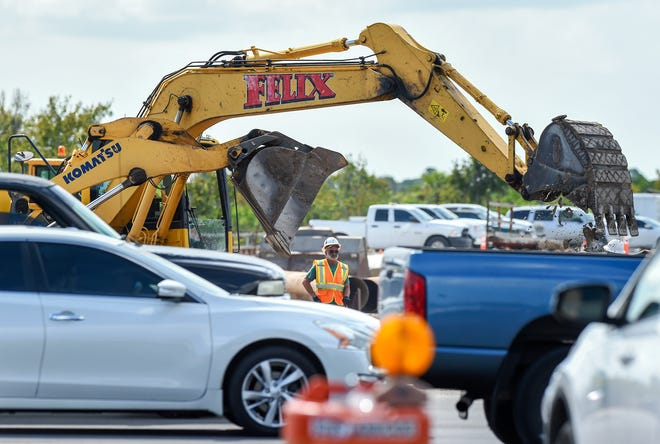 Construction workers labor to complete the final phase of the Crosstown Parkway Extension Project Wednesday, Oct. 10, 2018, as traffic flows by at the intersection of U.S. 1 and Southeast Village Green Drive in Port St. Lucie. Finishing the project is difficult due to the constrained work space and number of subcontractors all in one area, according to CPE Project Administrator George Denti.