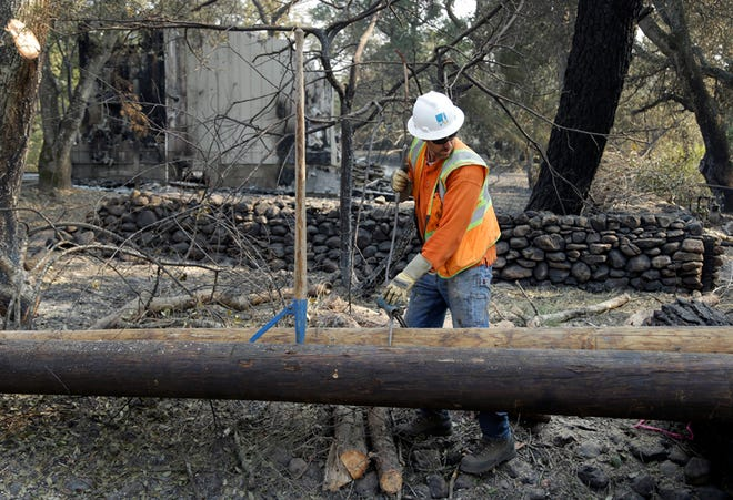 In this Oct. 18, 2017, file photo, a Pacific Gas & Electric worker replaces power poles destroyed by wildfires in Glen Ellen. California fire officials say sagging PG&E power lines that made contact ignited a blaze last year in California that killed four people and injured a firefighter.