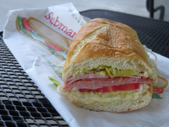 A sandwich layered with pepperoncini, freshly sliced meats, tomatoes and shredded lettuce is seen at La Mantia Italian Grocery in Ventura. Owner Bill Clark fought to get back the deli's familiar submarine-themed bags after a supplier discontinued them.