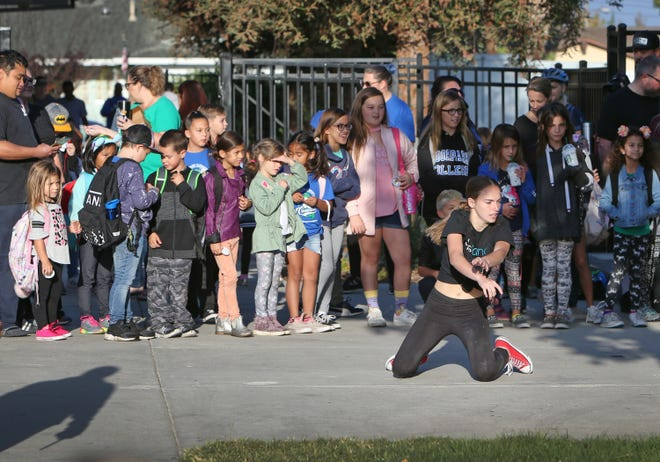Santa Susana High School senior Sarah Stickell, who takes a dance ensemble and choreography class, performs with her fellow dancers for Katherine Elementary students and their parents as the students head toward their classrooms. Wednesday was the school's annual Walk to School event. Santa Susana brought around 20 dancers to perform at the school.
