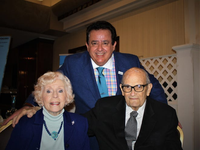 John DiAngelo, president and chief executive officer, Inspira Health Network (standing) poses with Catherine Gray Achée, and her husband C.J. Achée, at Inspira Auxiliary Cumberland County's Art Etc. event, which was held in Catherine's honor.