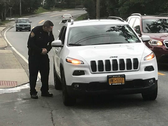 An Orangetown Police officer checks the ID of a Slocum Avenue resident before waving them through to their home, just feet from where officers and FBI agents have been conferring for hours. Oct. 10, 2018