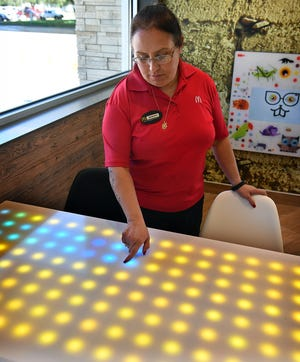 Yesenia Dominguez, a department manager for McDonalds, demonstrates the new interactive sparkle tables in the childrens area of the new McDonalds on Holliday Road.