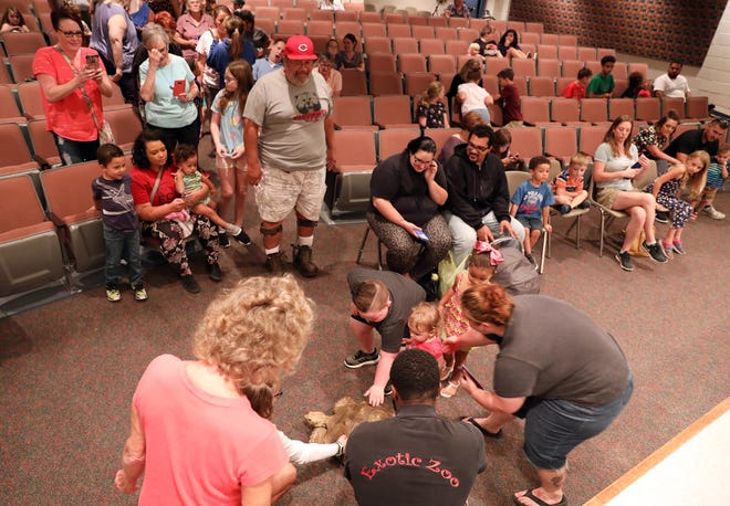 People gather around a tortoise at the John McIntire Library during a recent show by the Exotic Zoo in the library's auditorium. The Muskingum Library System, which has a levy on the fall ballot, is looking to engage with younger community members.