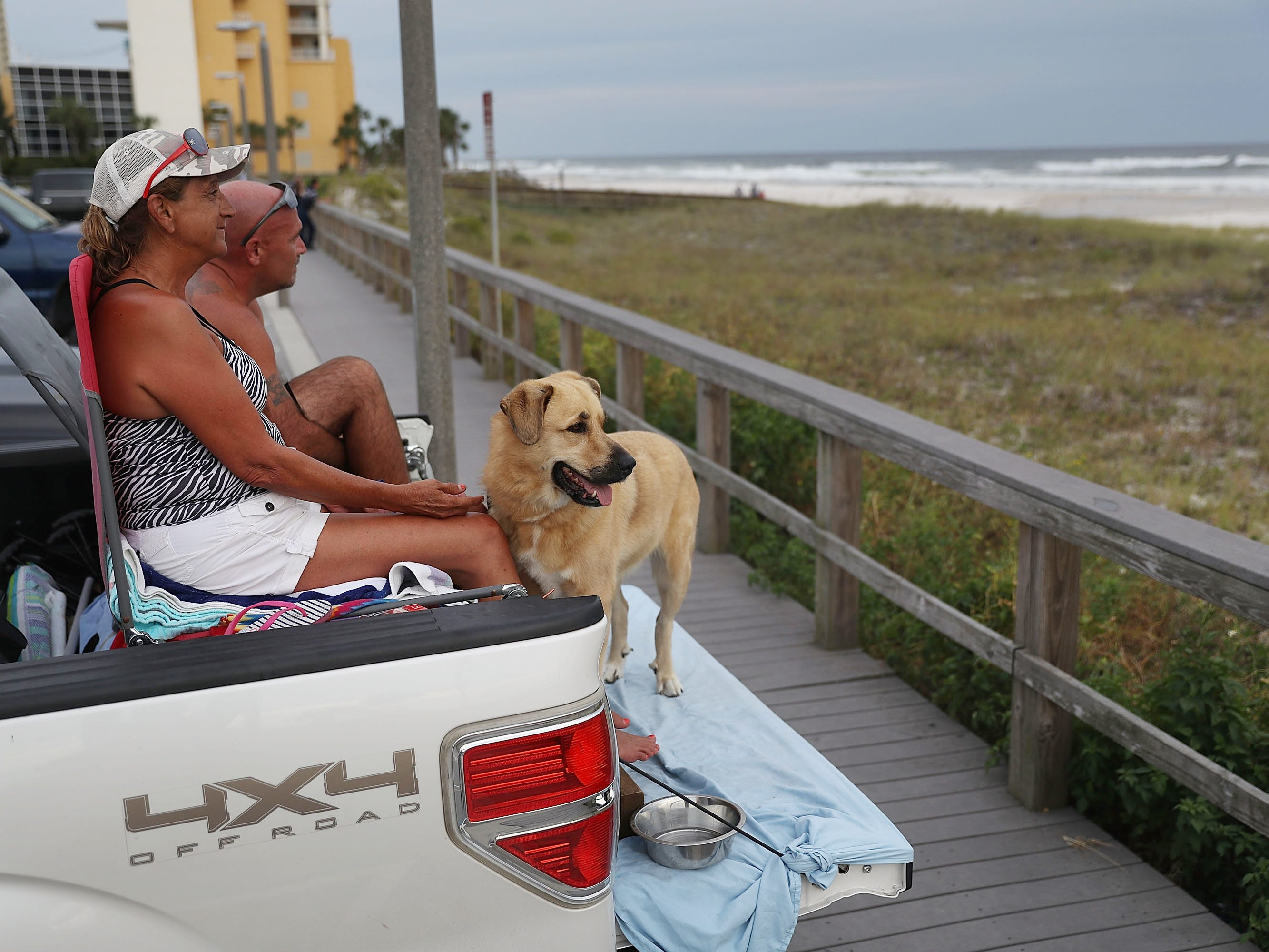 David Gage and Christal Gage and their dog, Bear, relax on the back of their pickup truck next to the ocean as they wait for the arrival of Hurricane Michael on Oct. 9, 2018, in Parker, Fla.