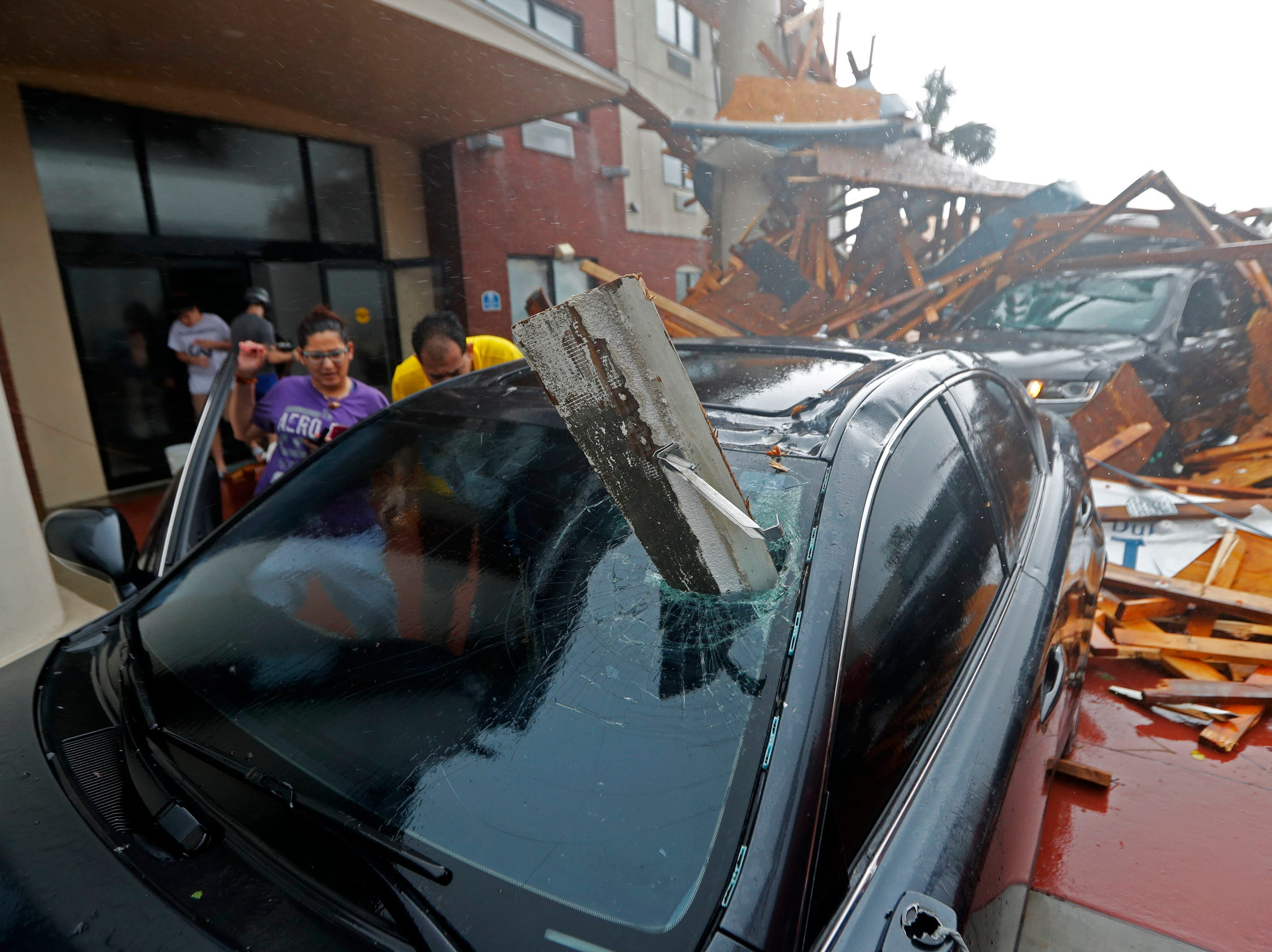 A woman checks on her impaled vehicle as Hurricane Michael passes through, after the hotel canopy had just collapsed, in Panama City Beach, Fla., on Wednesday.