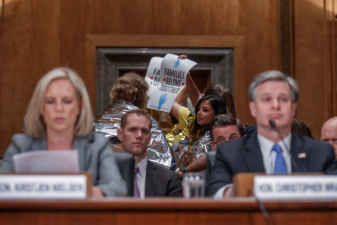 Activists protest as Secretary of Homeland Security Kirstjen Nielsen (L) and FBI Director Christopher Wray testify during the Senate Homeland Security and Governmental Affairs Committee hearing on Capitol Hill in Washington, D.C., on Oct. 10, 2018.