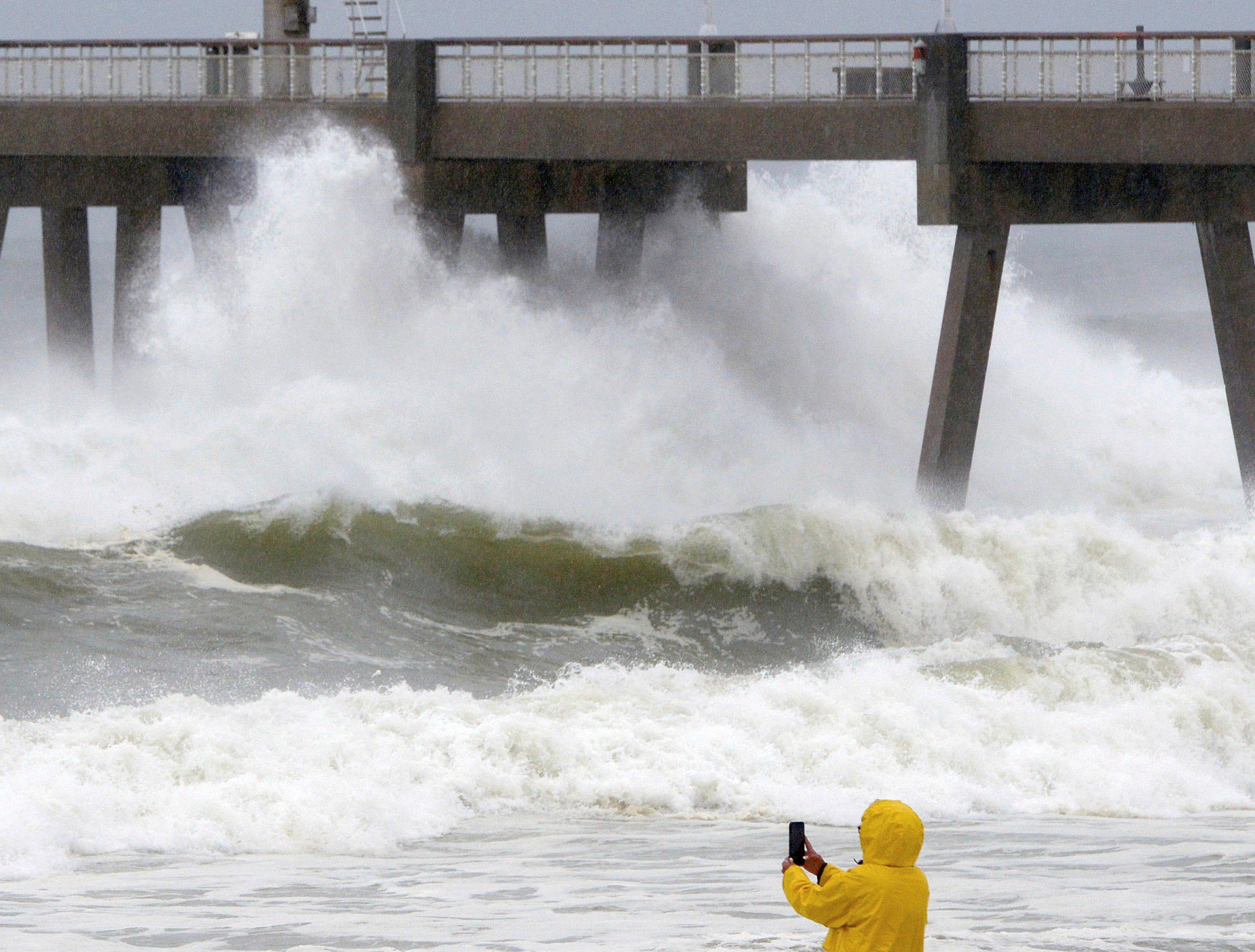 A beachgoer take photos of the waves on Oct. 10, 2018, on Okaloosa Island in Fort Walton Beach, Fla., behind the boardwalk as Hurricane Michael impacts the coast.