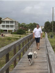 Roger Malone of Decatur, Tennessee. walks Oct. 9, 2018, toward the beach on St. George Island, Florida, ahead of Hurricane Michael. Malone and his partner, Angela Ferguson, chose not to  evacuate despite a mandatory  order for all of Franklin County.