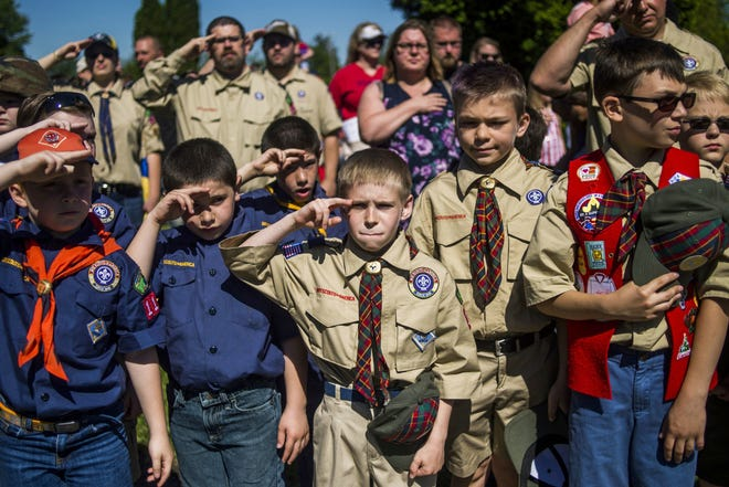 Boy Scouts and Cub Scouts salute in Linden, Mich. May 29, 2017