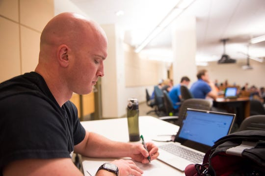 Halston Drennan takes notes during his calculus III course at the University of Wyoming. Drennan used to teach high school math in Fort Collins, Colorado but decided to go back to engineering school after pay for his teaching job couldn't keep up with his living expenses.