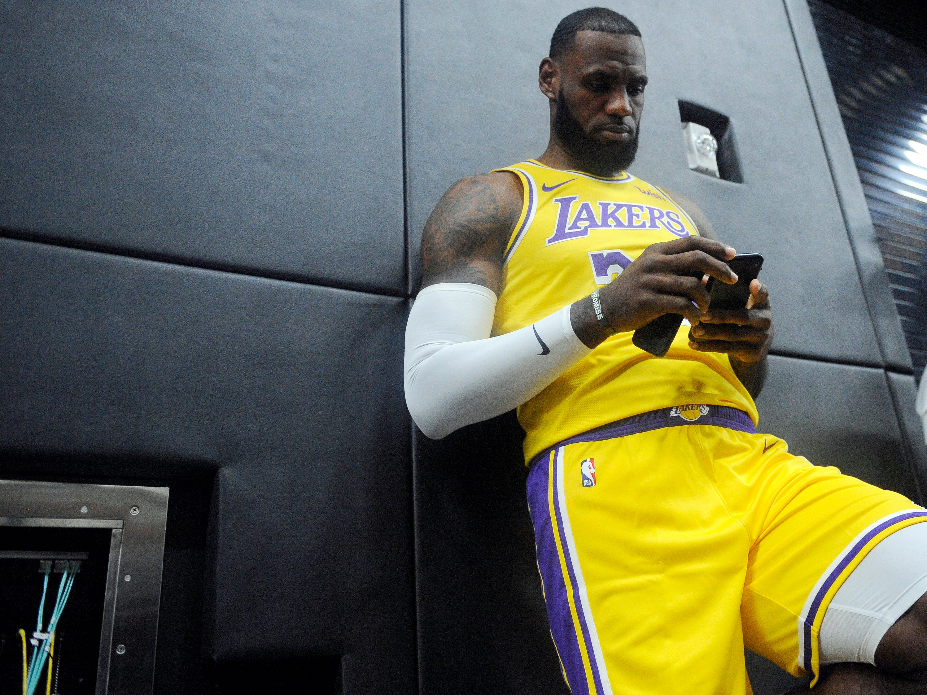 James takes a moment to check his phone during media day.