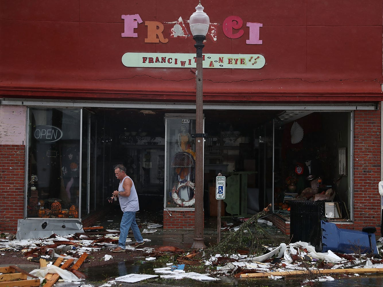 People walk past damaged stores after hurricane Michael passed through the downtown area in Panama City.