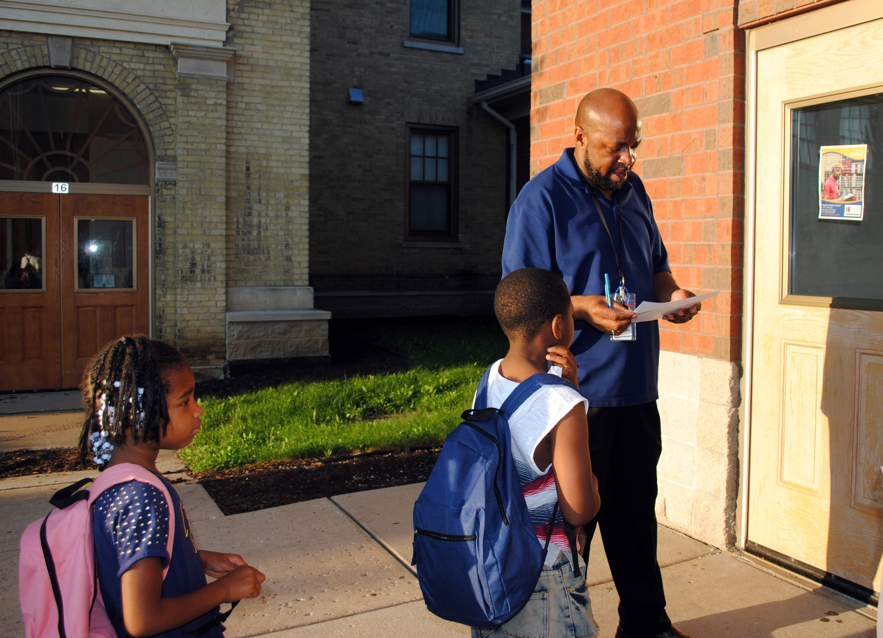 Edward Lawson checks to see if a student is on the list to enter the before-school activities program at Julian Thomas Elementary School in Racine, Wisconsin.