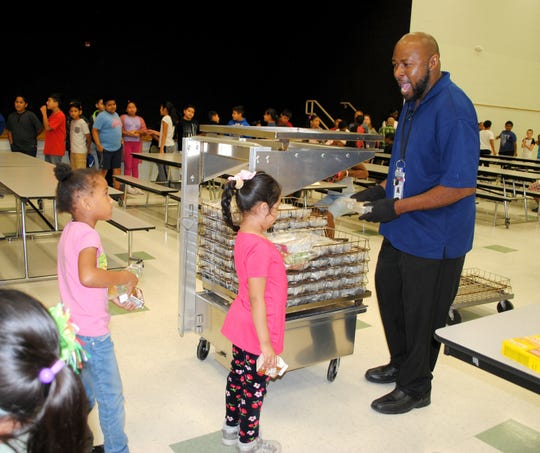 Edward Lawson, a home substitute at Julian Thomas Elementary School in Racine, Wisconsin, reacts with a smile to a student as he hands out lunches. Lawson has been with the Racine Unified School district for the past 18 years. A home substitute is different from a regular substitute in that he works every day at the same school and is used to fill in where needed. As a result, Landers wears many hats and does a wide variety of jobs.