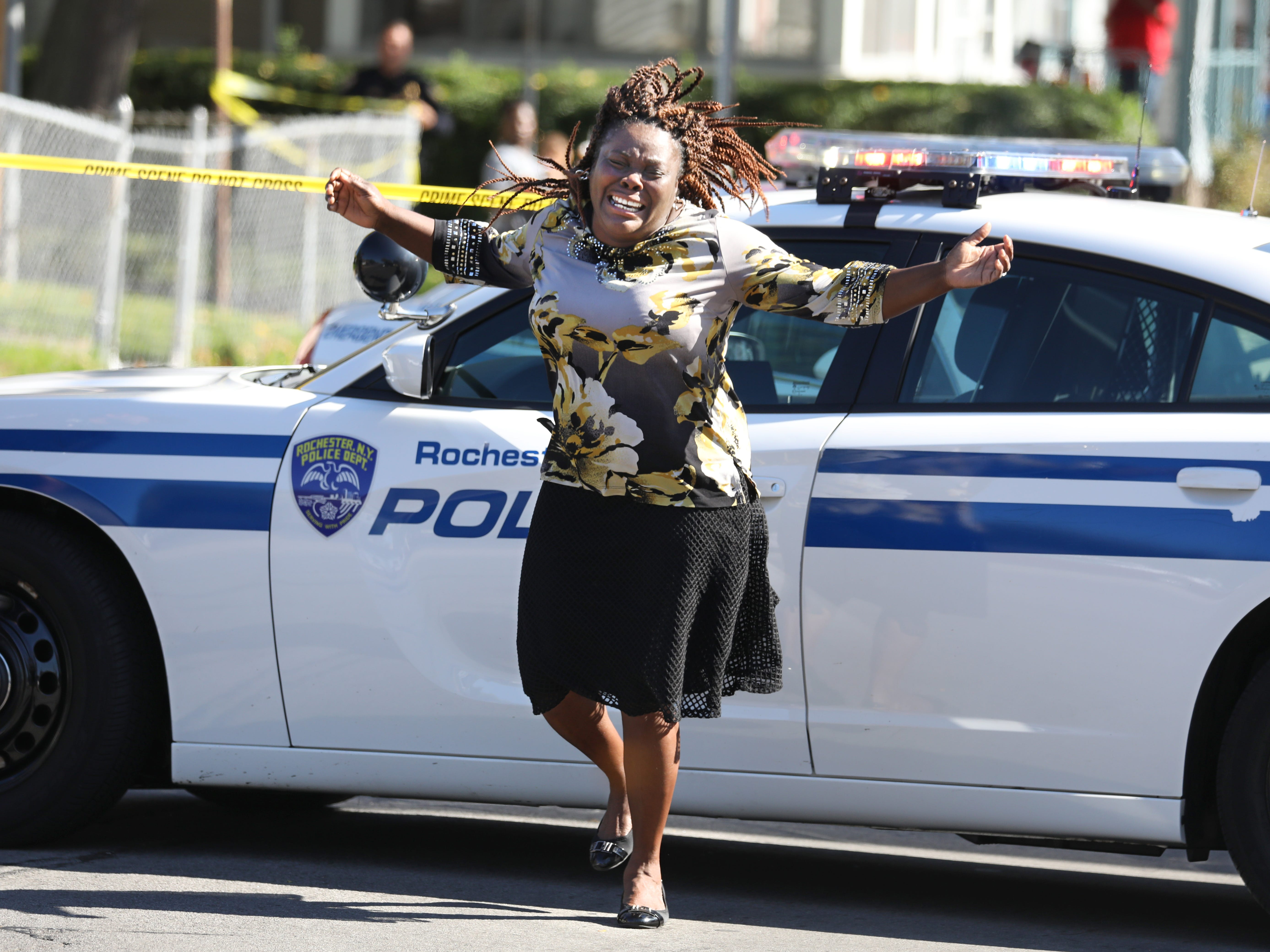Juliet Blake-Lavan, of Rochester, the aunt of the shooting suspect, reacts at a police roadblock near the scene on Bay Street in Rochester, N.Y., Wednesday, Oct. 10, 2018. A man fatally shot a woman with whom he had a relationship and wounded his own son and a second man Wednesday, then was killed by police in a shootout during a vehicle chase through a Rochester neighborhood.